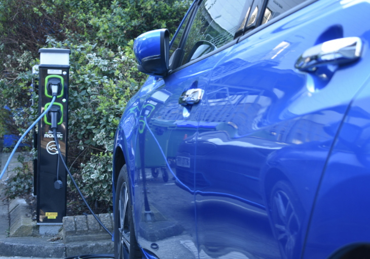 Blue car on charge next to charge point