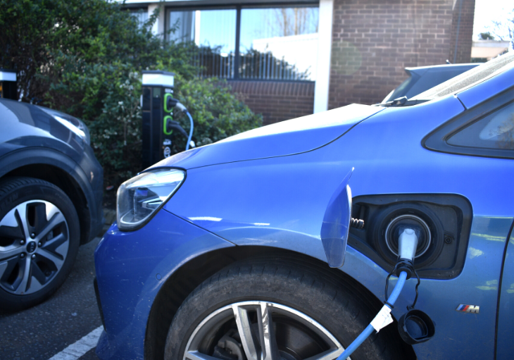 Electric car being charged via charge point